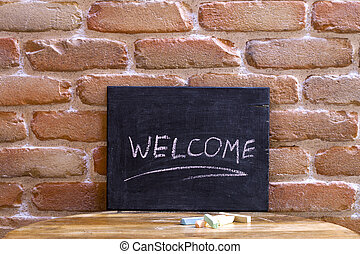 Black board with the word WELCOME drown by hand on wooden table on brick wall background.
