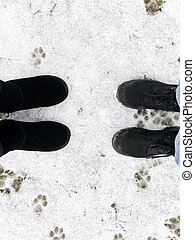Black boots in the winter on snow and grass