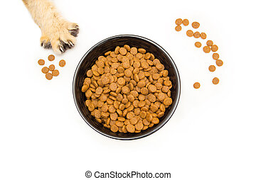 Black bowl with dry cat food stands on a white background top view