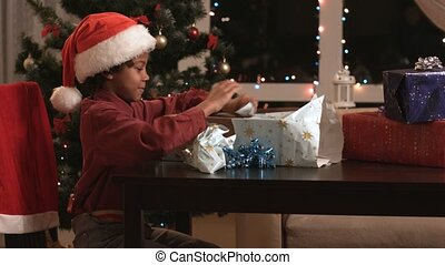 Black boy opening Christmas present.