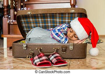 Black boy sleeps in suitcase.