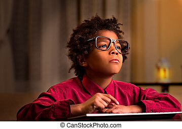 Boy in glasses using keyboard.