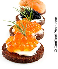 Black bread topped with salmon, trout, sturgeon caviar and ...