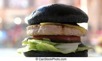 Black bun burger. Meat and lettuce leaves.