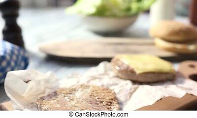 Black burger bun and lettuce. Slices of pickled cucumber.