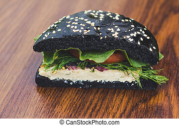 black burger on a board of wood