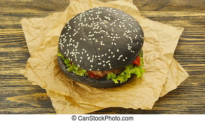 Black burger on wooden table - Gourmet black burger with...