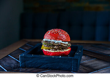 Black burger with prawns on wooden board - Close up ...