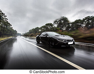 Black business class driving in the rain
