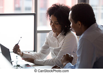 Black business partners sitting at desk looking at computer screen