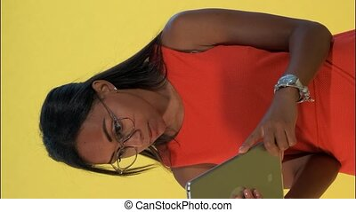 Black business woman in dress and eyeglasses analysing something on tablet There is yellow background. Video with Vertical Screen Orientation 9:16