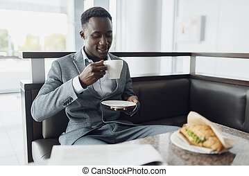 Black businessman having lunch in office cafe