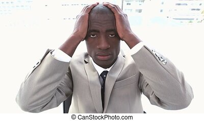 Black businessman holding his head in his hands