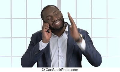 Black businessman in suit having phone coversation.