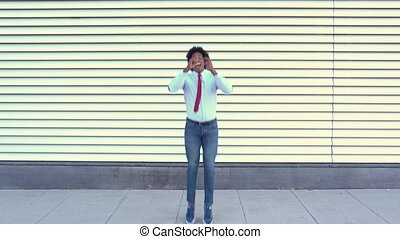 Black Businessman jumping outdoors. Man with afro hair. - ...
