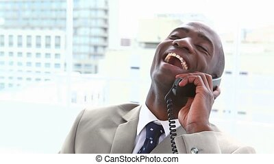 Black businessman laughing on the phone in his office