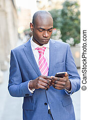 Black businessman reading his smartphone in urban background
