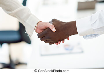 Black businessman shaking hands with a caucasian businesswoman