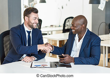Black businessman shaking hands with a caucasian one in office