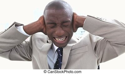 Black businessman shouting the hands on his ears