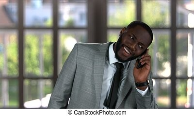 Black businessman talking on phone.