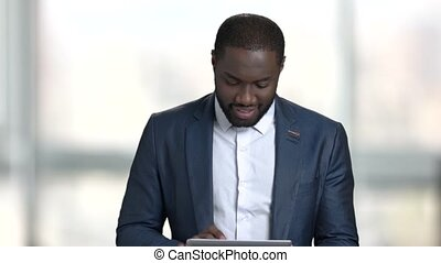 Black businessman tapping on tablet screen.