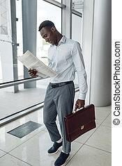 Black businessman with briefcase reading newspaper