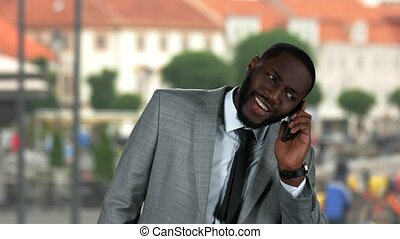 Black businessman with phone smiling.