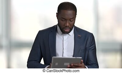 Black businessman with touchscreen tablet device.