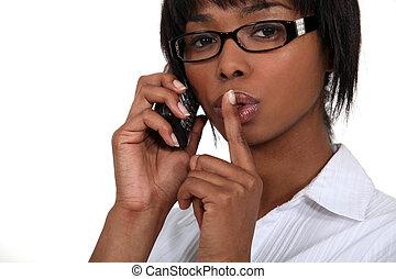 Black businesswoman making hush gesture during phone call
