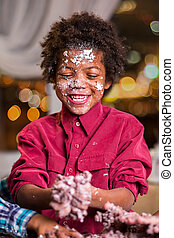 Black cake-smeared boy laughing.