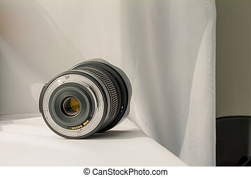 Black camera zoom lens on white cloth