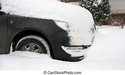Black car covered in deep winter snow. Car after heavy snow...