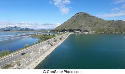 Black car driving on bridge blue sea, mountains and sky background. Footage. Car going on a road near the river, aerial view. Footage. Aerial view at small forest lake and line of highway passing near.