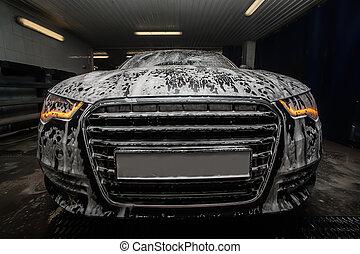 Black car in foam on a car wash