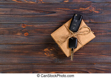 Black car key in a present box on wooden table