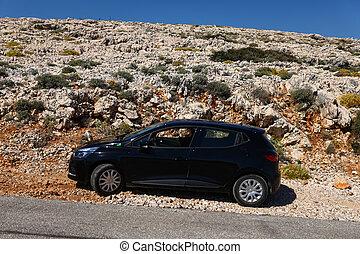 Black car on the rocky road in Croatia, hot summer