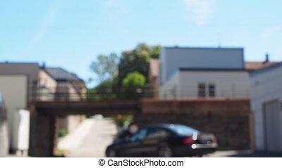 Black car passing under a old fashioned rocky train bridge -...