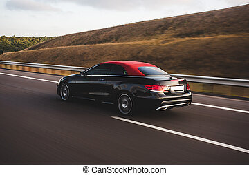 Black car with red tuning driving on the road