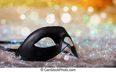 Black carnival mask on bokeh background