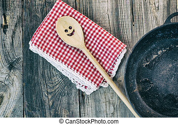 Black cast-iron frying pan with a wooden spatula for...