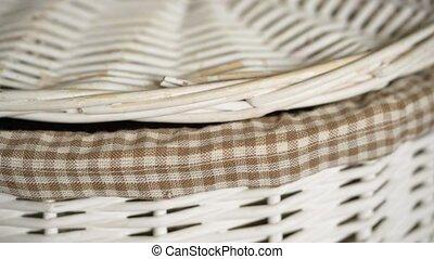 Black cat peeking out of a wooden basket