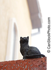 Black cat statue on the stone wall with path