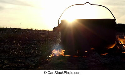 Black cauldron stands in a campfire. It boils hot water at sunset in slow motion