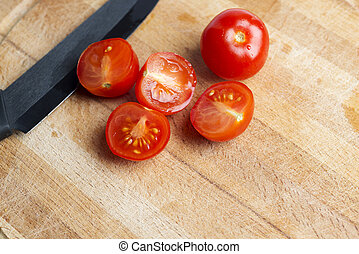 Black ceramic knife on a wooden Board with cherry tomatoes.