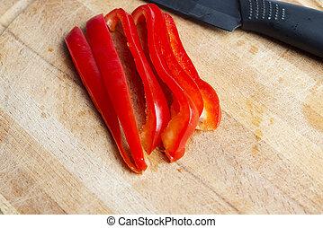 Black ceramic knife on wooden Board c red pepper.