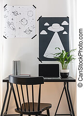 Black chair at desk with laptop and plant in home office interior with posters on white wall. Real photo