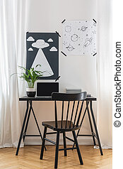 Black chair at desk with laptop and plant in white home office interior with posters. Real photo