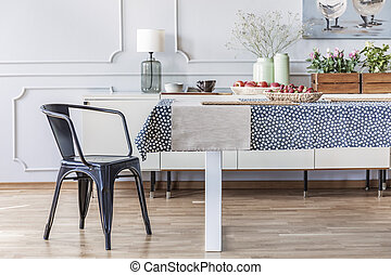 Black chair at table in white eclectic dining room interior with wall with molding. Real photo