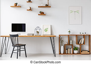 Black chair at table with computer monitor in bright home office interior with poster. Real photo